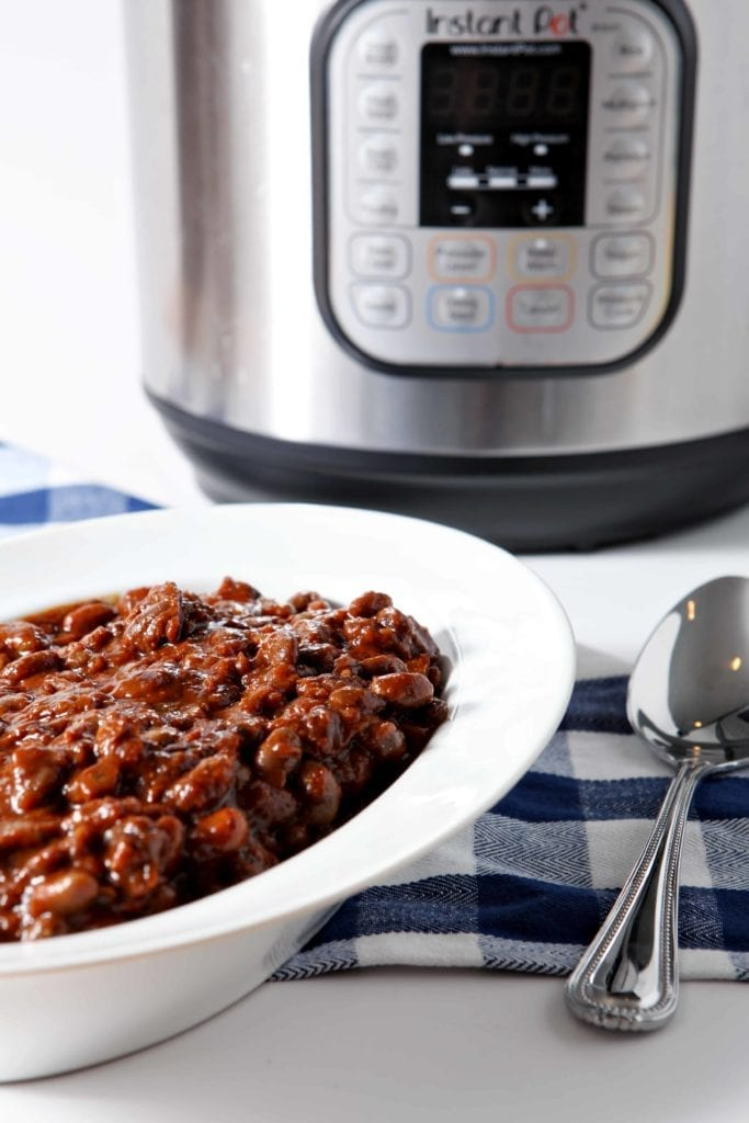 Instant Pot Vegetarian Baked Beans are served in a white bowl in front of an Instant Pot