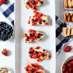 Patriotic Strawberry Bruschetta are served on a white platter, sitting atop a white background and a blue buffalo plaid napkin. The bruschetta are surrounded by strawberries, blueberries, lemon curd, pudding and grilled angel food cake, which all go into the making of the bruschetta.