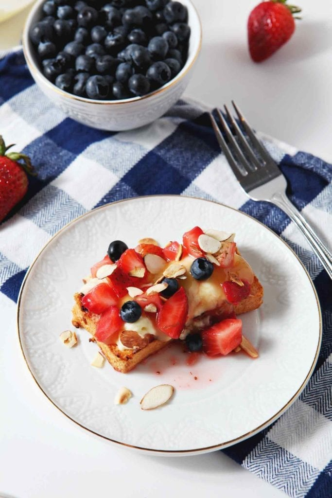 A piece of Patriotic Strawberry Bruschetta, layered beautifully, is served on a white dessert plate on top of a blue buffalo plaid napkin. Shown with a fork, fresh strawberries and blueberries in the background.