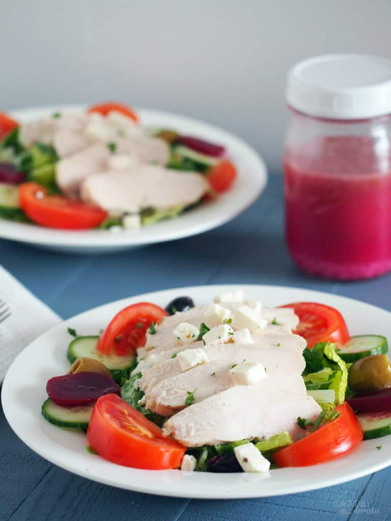 A white plate holds a serving of colorful Chicken Greek Salad