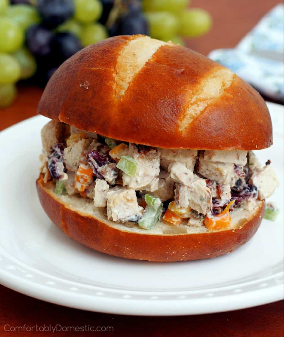 A Chicken Salad Sandwich with Lemon Dill Yogurt Dressing sits on a white plate