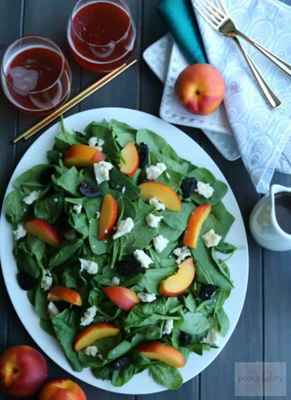 A big white bowl holds a Nectarine Blue Cheese Spinach Salad for a crowd