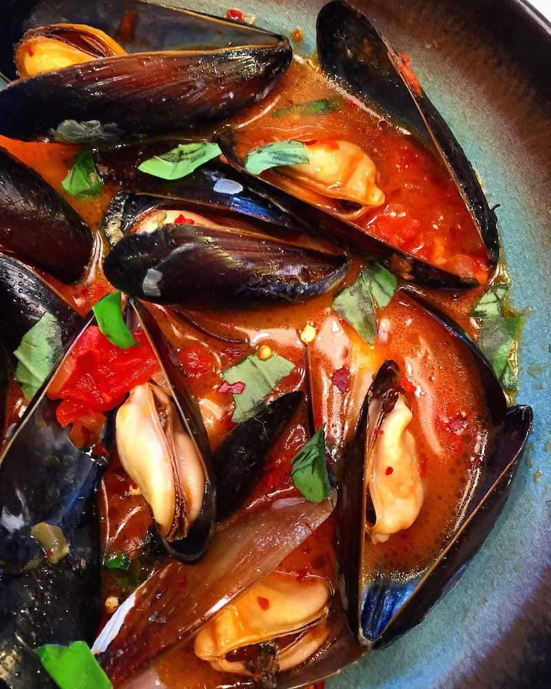Spicy Mussels with Wine and Chorizo sit in a neutral-colored bowl, ready for eating