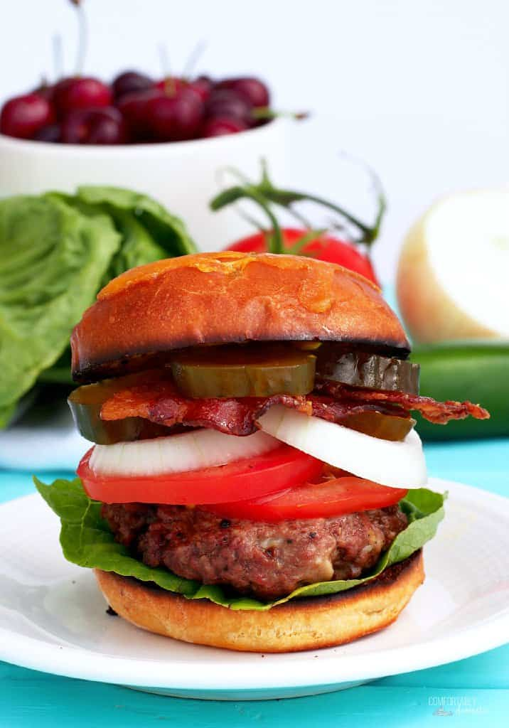 A Sweet Heat Burger sits on a white plate before serving, topped with onions, lettuce and tomatoes.