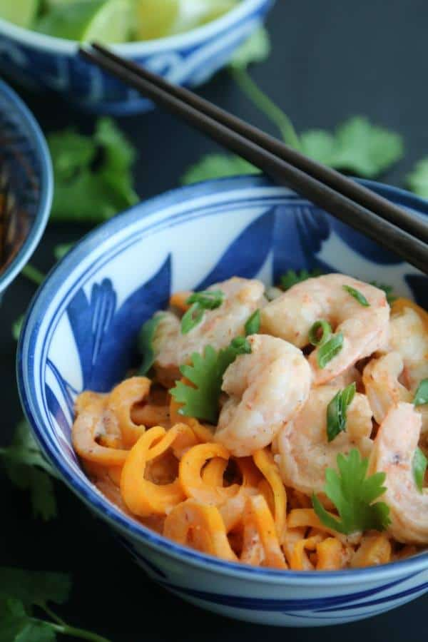 A blue bowl holds Thai Red Curry Coconut Shrimp and Sweet Potato Noodles