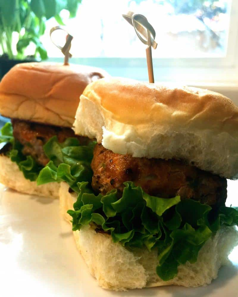 Two Turkey Shisito Burgers sit on a white platter before serving