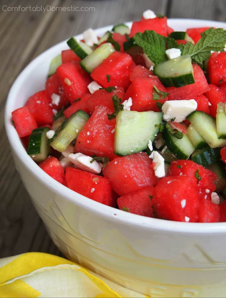 A white bowl holds Watermelon Cucumber Salad with Feta, Mint, and Lime