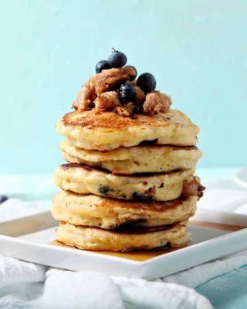 A stack of Blueberry Breakfast Sausage Pancakes sits on a square plate, covered in maple syrup.