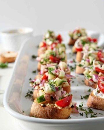 Greek Bruschetta sit on a white platter at a party before serving