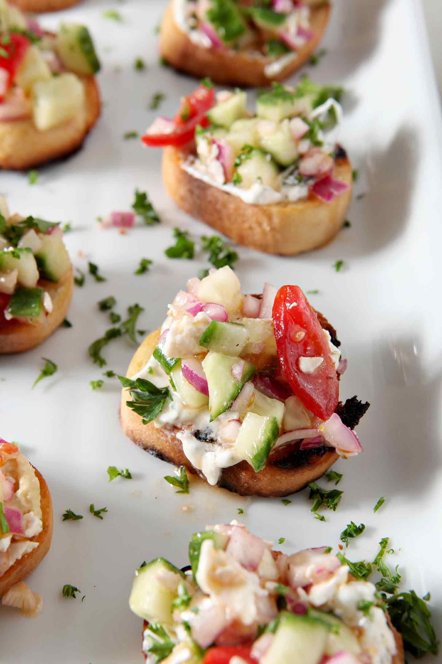 A close up image of the final Greek Bruschetta, garnished with parsley and served on a white platter