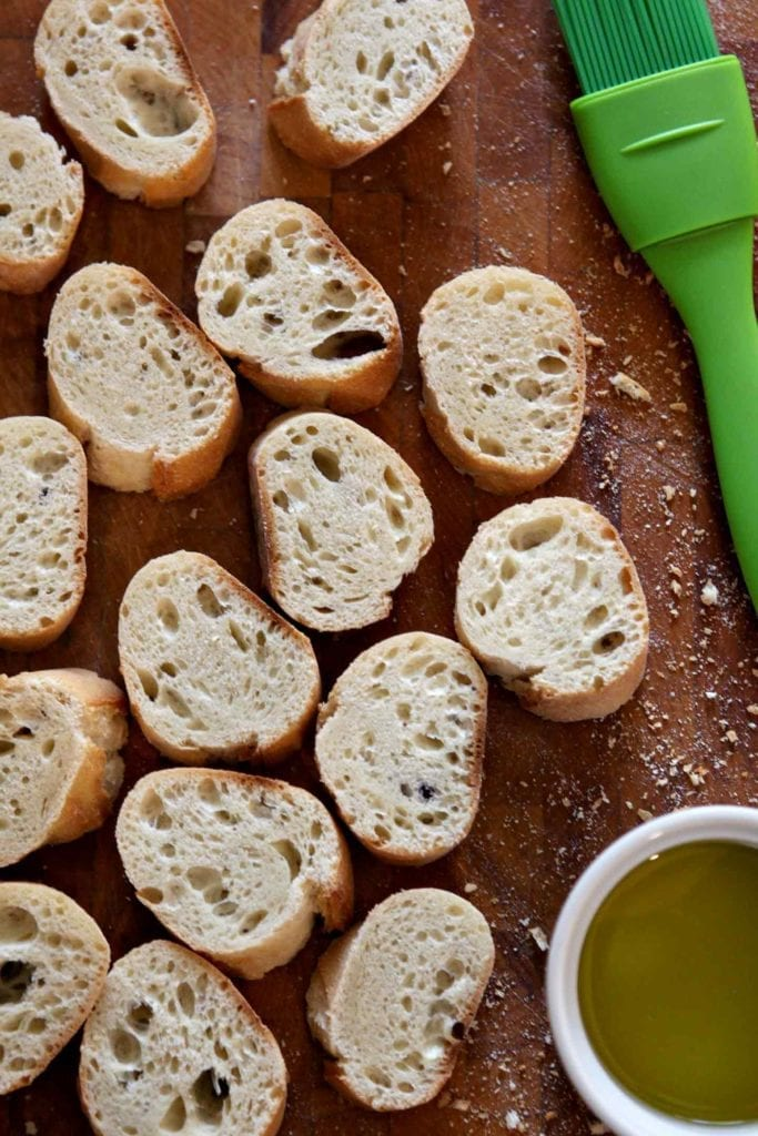 Bread slices sit on a cutting board with a bowl of olive oil and a pastry brush before grilling