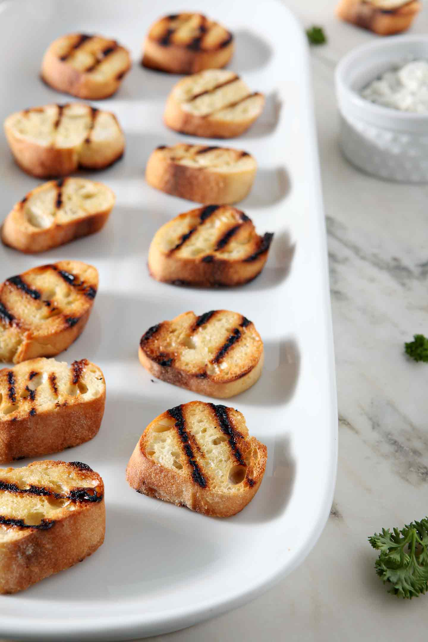Grilled bruschetta rounds sit on a white porcelain platter before being topped with ingredients
