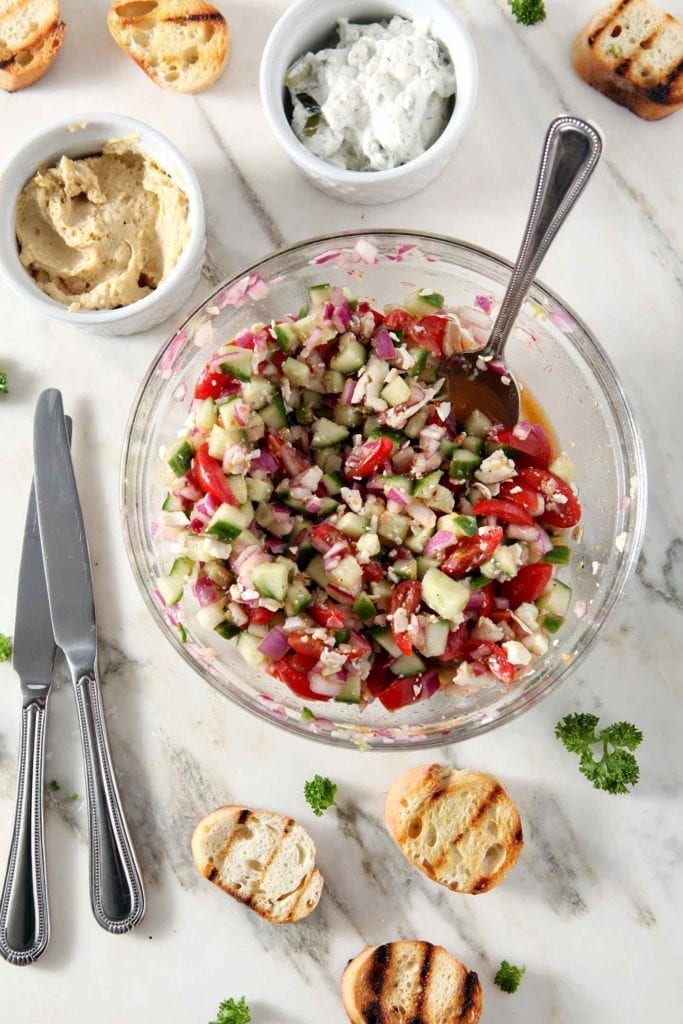 The cucumber and tomato topping sits in a glass bowl, surrounded by toasted garlicky bread, hummus and tzatziki sauce before Greek Bruschetta is put together.