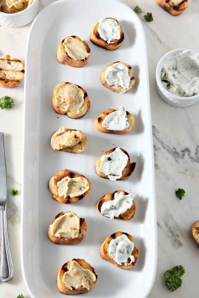 Hummus and tzatziki sauce are spread on top of toasty baguette rounds before bruschetta is assembled.