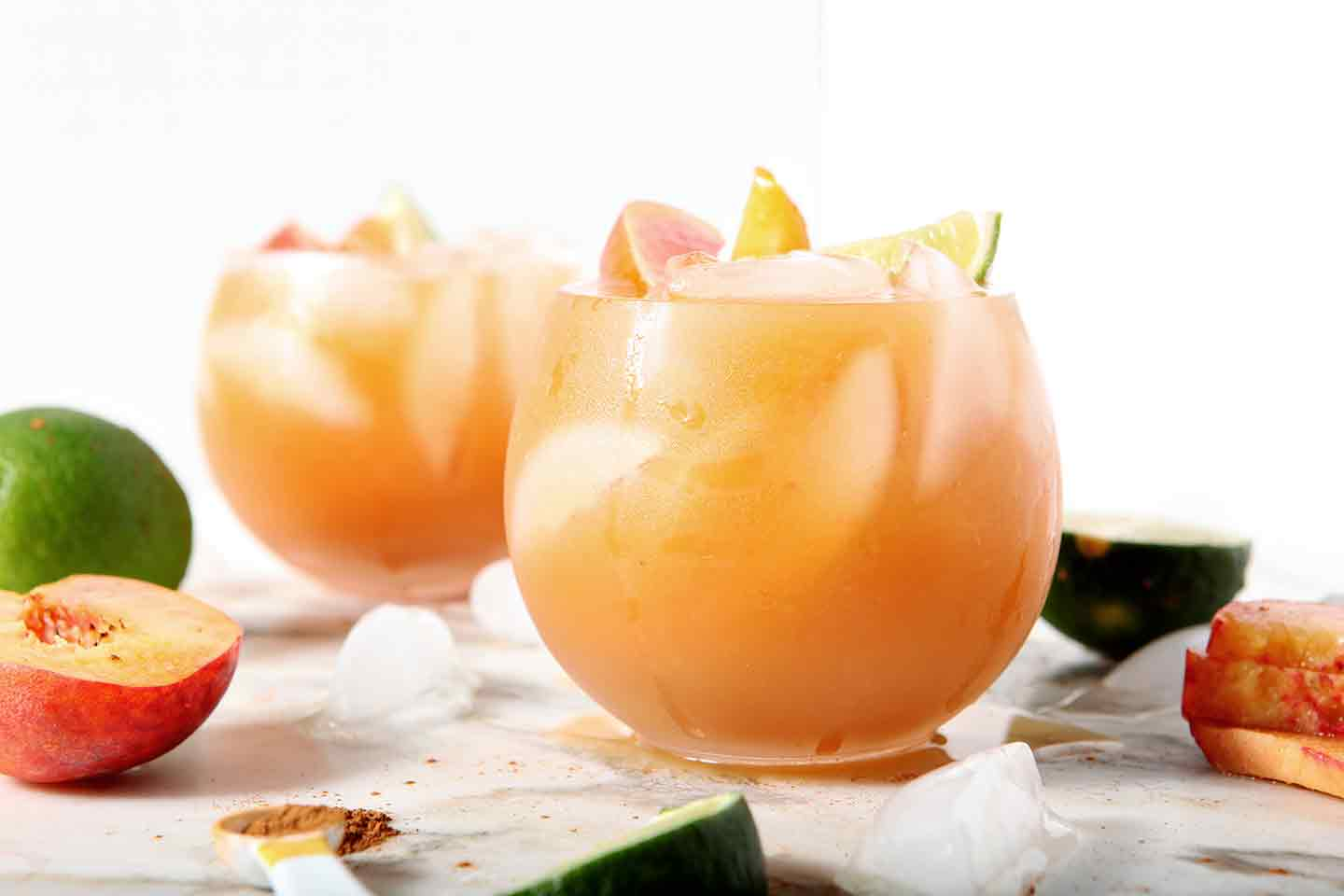 Two Peach Moscow Mules sit on a marble background surrounded by ice, lime wedges and peach slices