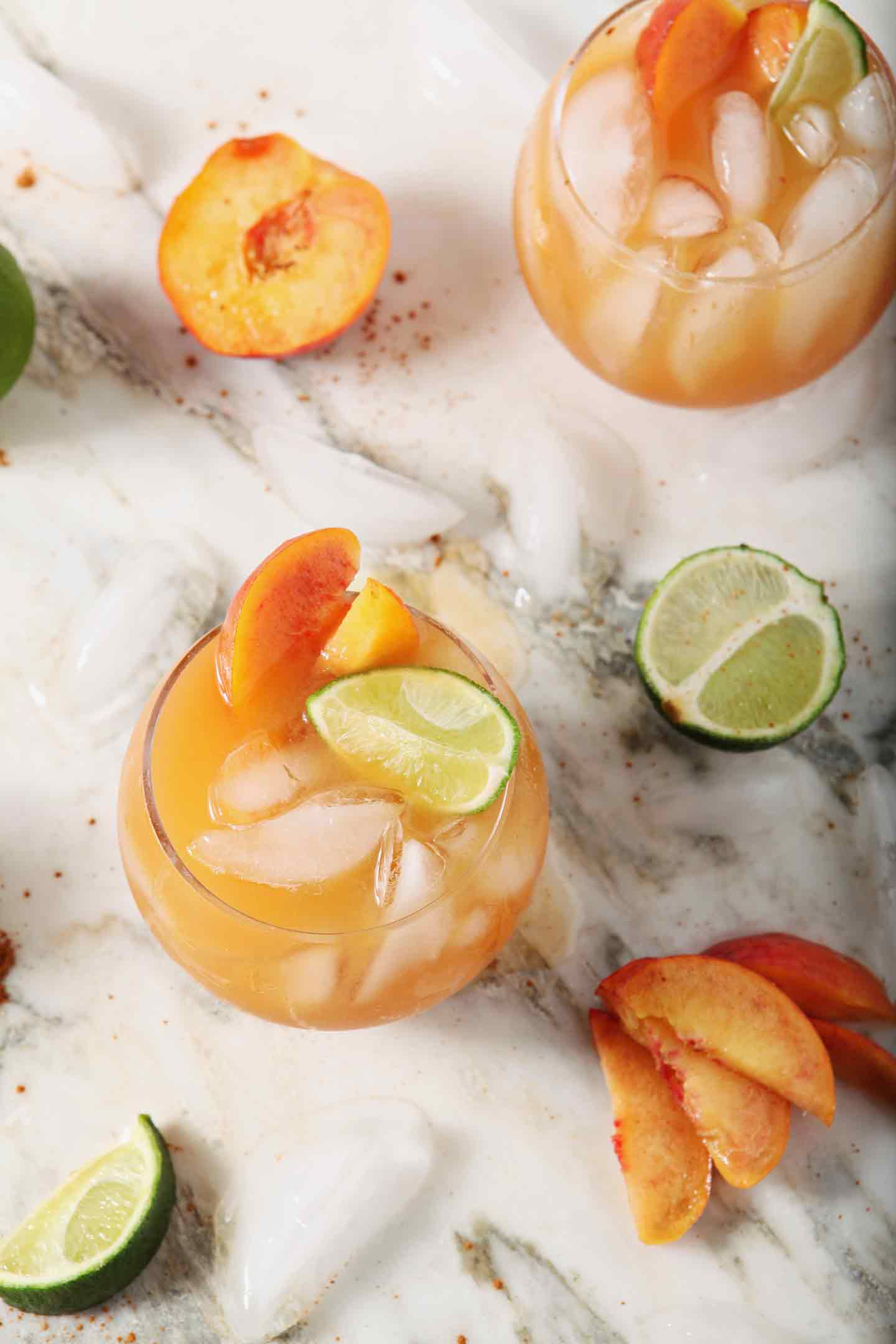 Overhead image of two Peach Moscow Mules, garnished with peach slices and lime wedges