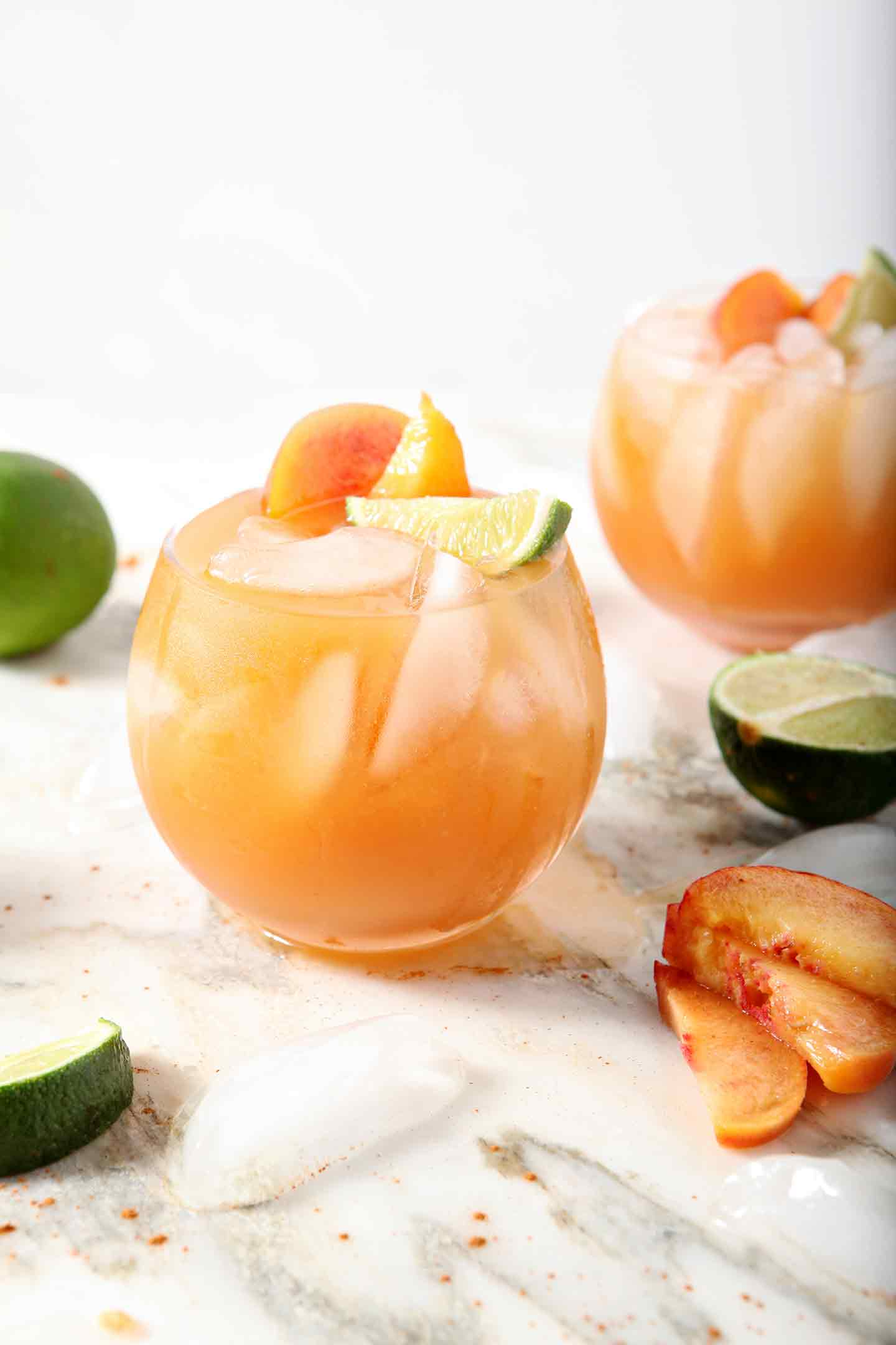 Two Peach Moscow Mule sit on a marble background, surrounded by peach slices and limes