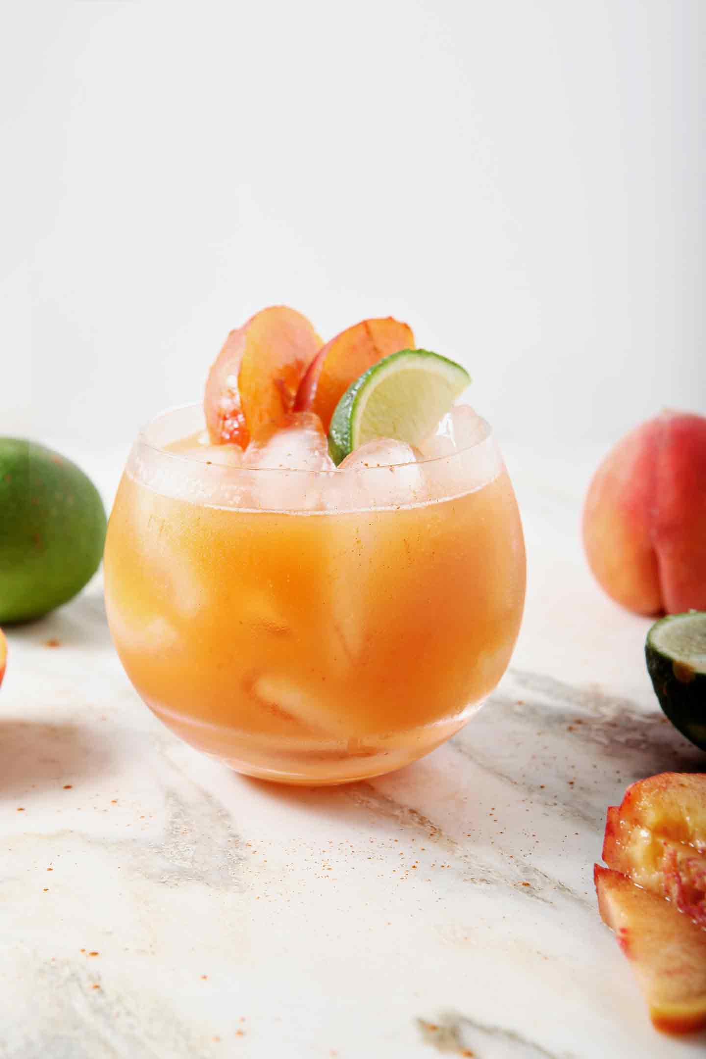 A lone Peach Moscow Mule sits on a marble background, surrounded by peaches and limes