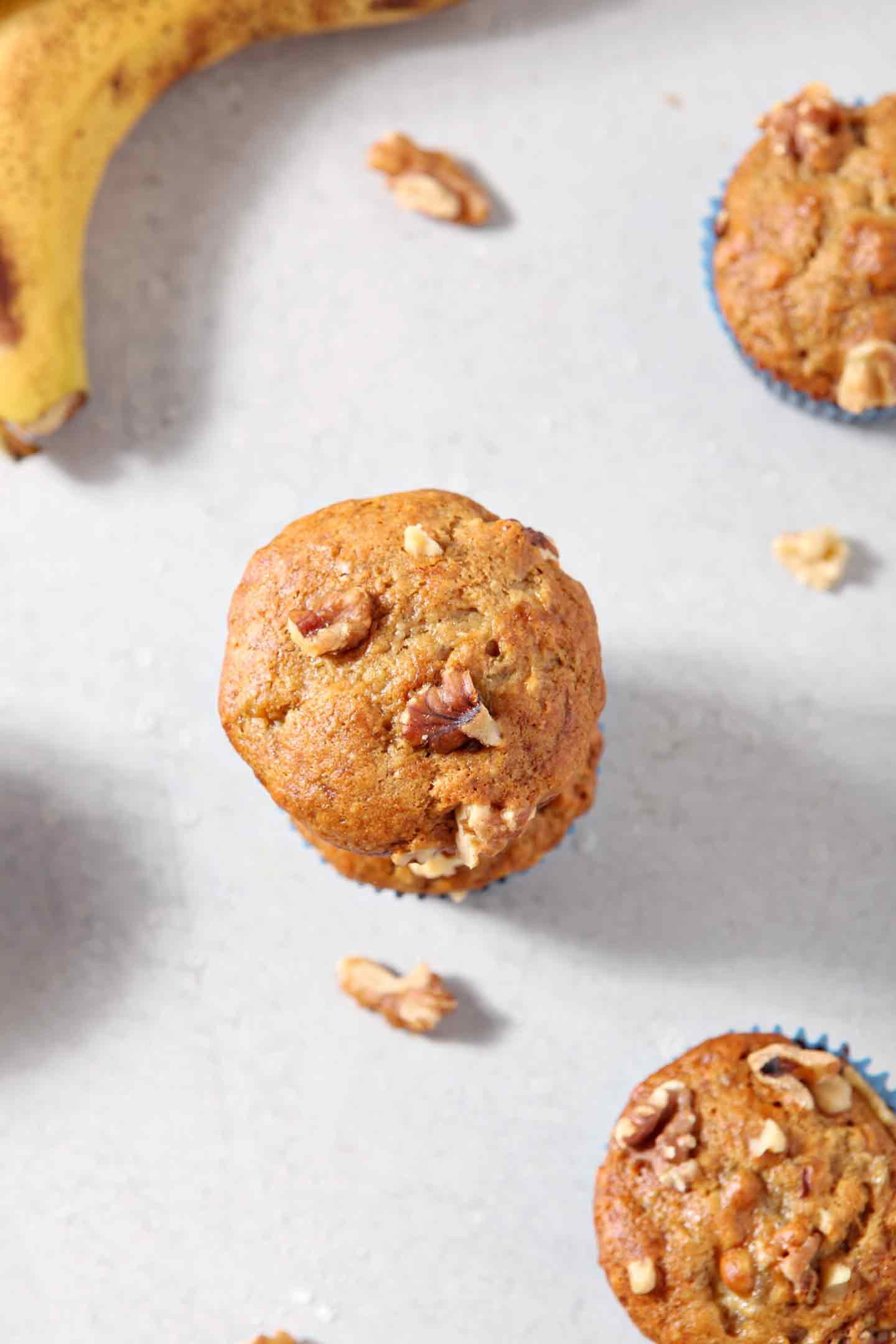Overhead image of Vegan Banana Muffins, shown with walnuts and bananas