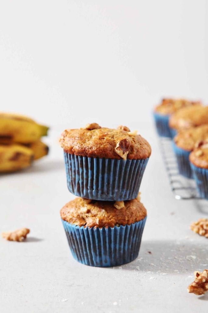 Two Vegan Banana Muffins are stacked on top of one another. Bananas and other muffins appear in the background.