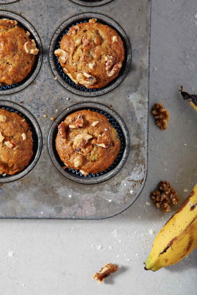 Vegan Banana Muffins sit in the muffin tin after coming out of the oven