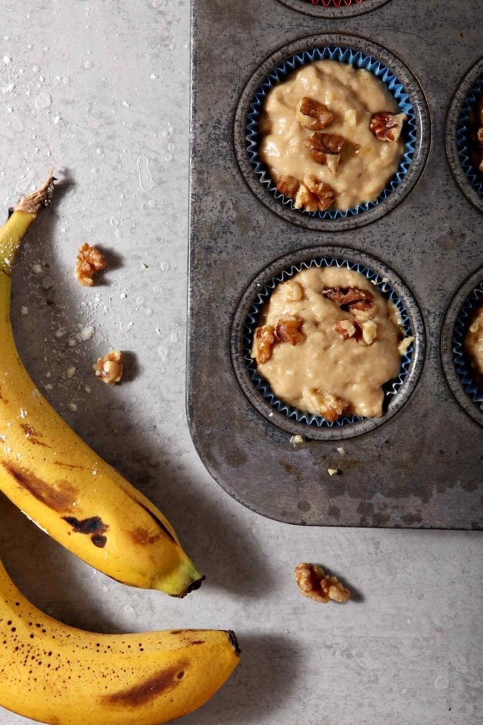 The batter for the Vegan Banana Muffins sits inside the muffin tin, ready for baking