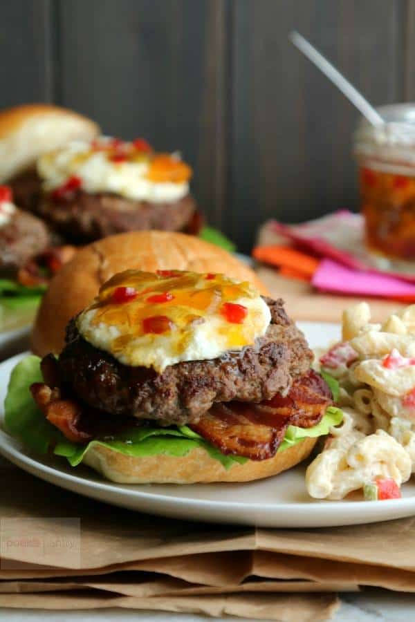 A Bacon Goat Cheese Burger, topped with pepper jam, sits on a white plate with potato salad