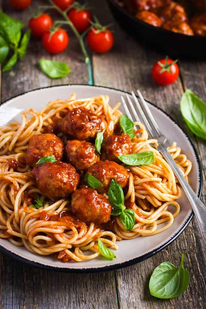 Instant Pot Spaghetti and Meatballs is served on a plate, surrounded by fresh basil and tomatoes