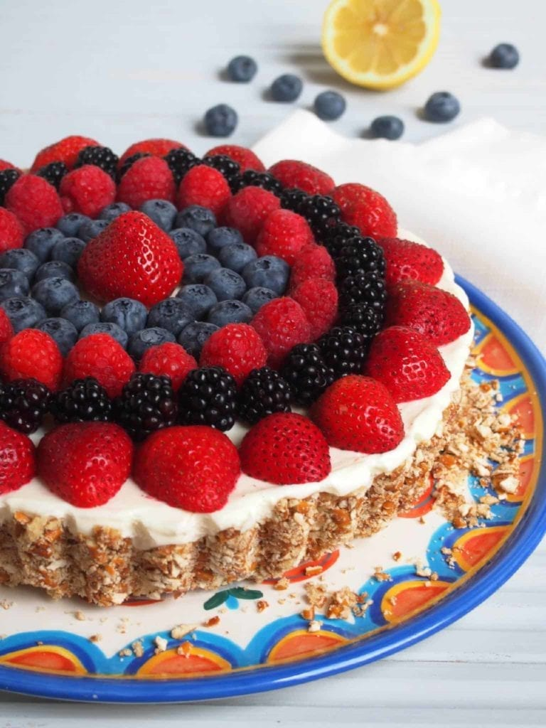 A No Bake Lemon Mousse Tart with Pretzel Crust sits on a colorful plate, topped with fresh fruit