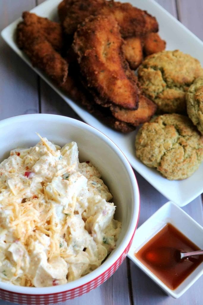 Overhead image of Pimento Cheese Potato Salad, Chicken Tenders and Potato Biscuits, all served together on a wooden background