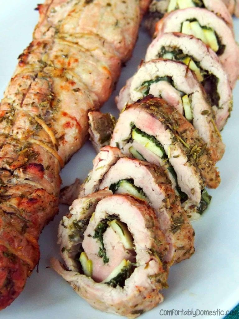 Sliced Rosemary Pesto Pork Roulades sit on a white platter