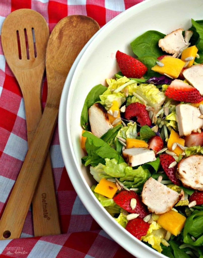 A large bowl is Strawberry Mango Salad with Chicken and Fresh Strawberry Poppyseed Vinaigrette is shown with wooden utensils, ready for serving