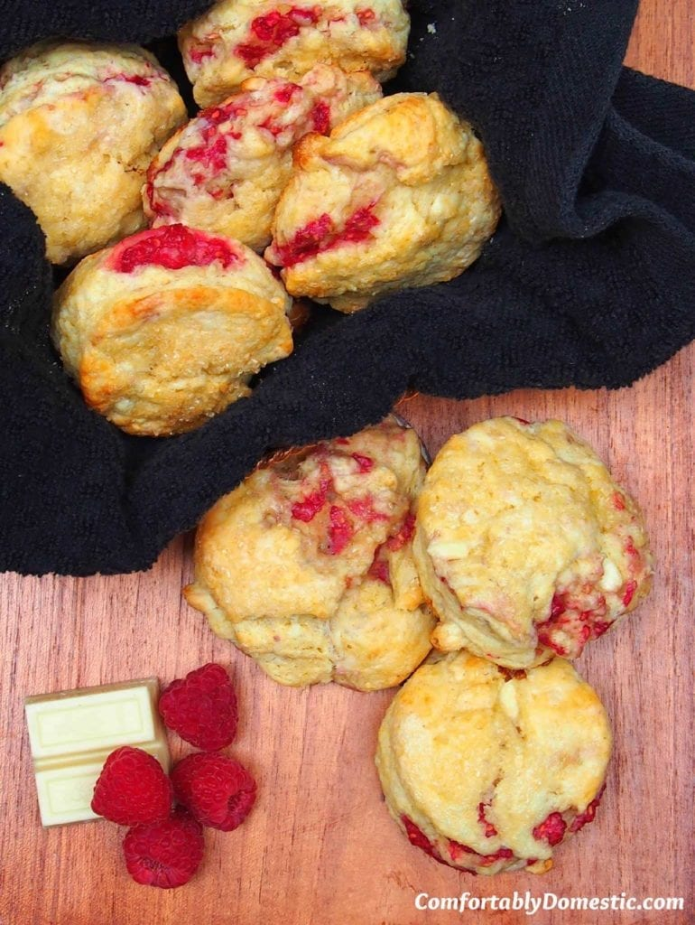 White Chocolate Raspberry Scones are shown from above and served on a wooden platter with fresh raspberries and a dark colored napkin