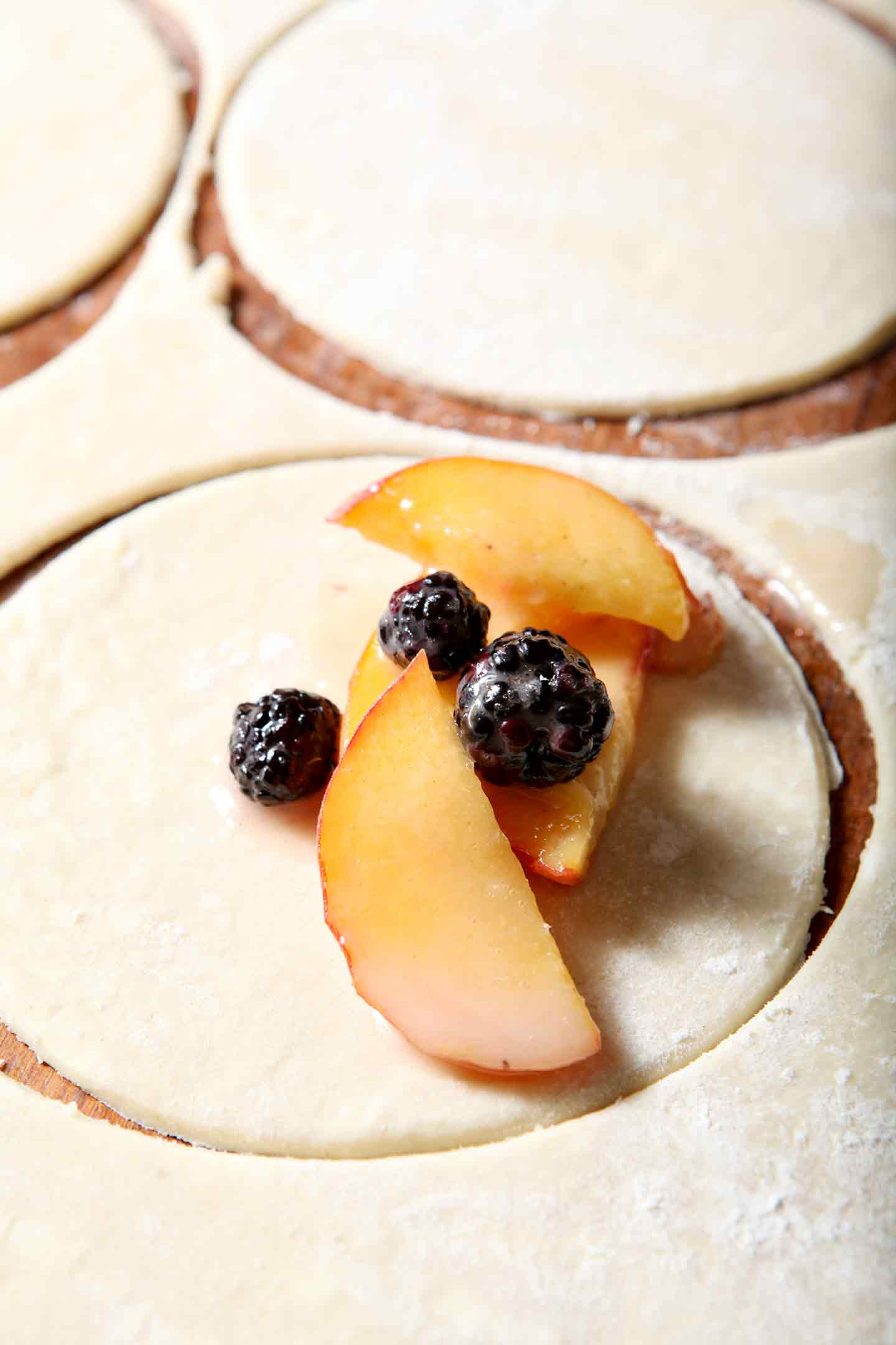 Sliced peaches and blackberries are placed in a pie crust round