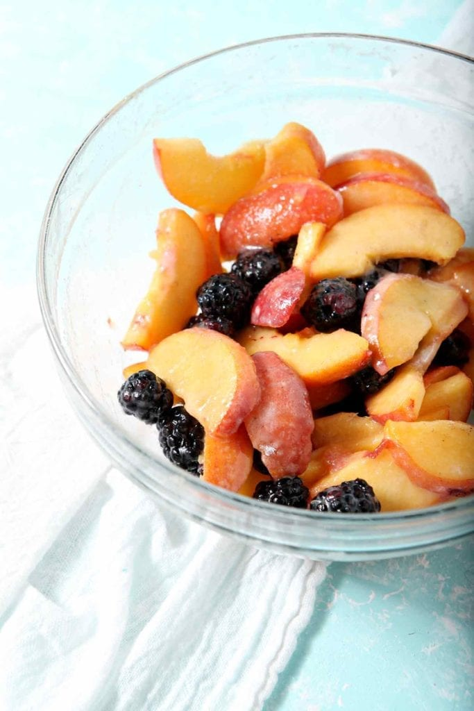 Sweetened blackberries and peach slices in a bowl