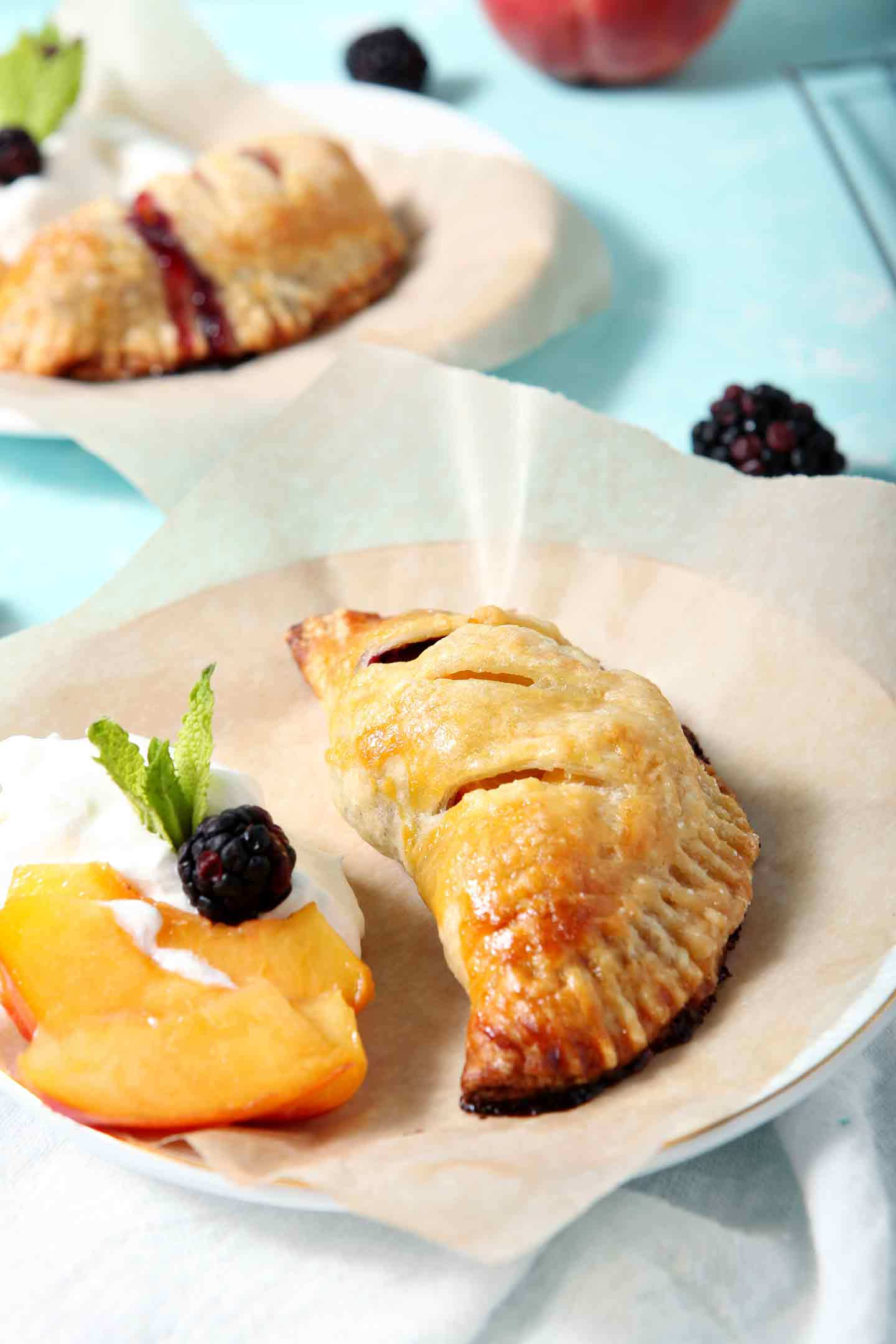 A Blackberry Peach Hand Pie sits on a plate with Bourbon Whipped Cream, peach slices and blackberries