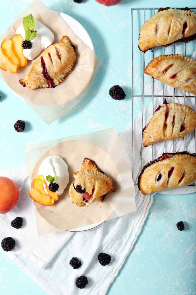 Several Blackberry Peach Hand Pies are served with Bourbon Whipped Cream on an aqua background