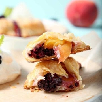 A Blackberry Peach Hand Pie is shown on a plate, halved, with Bourbon Whipped Cream