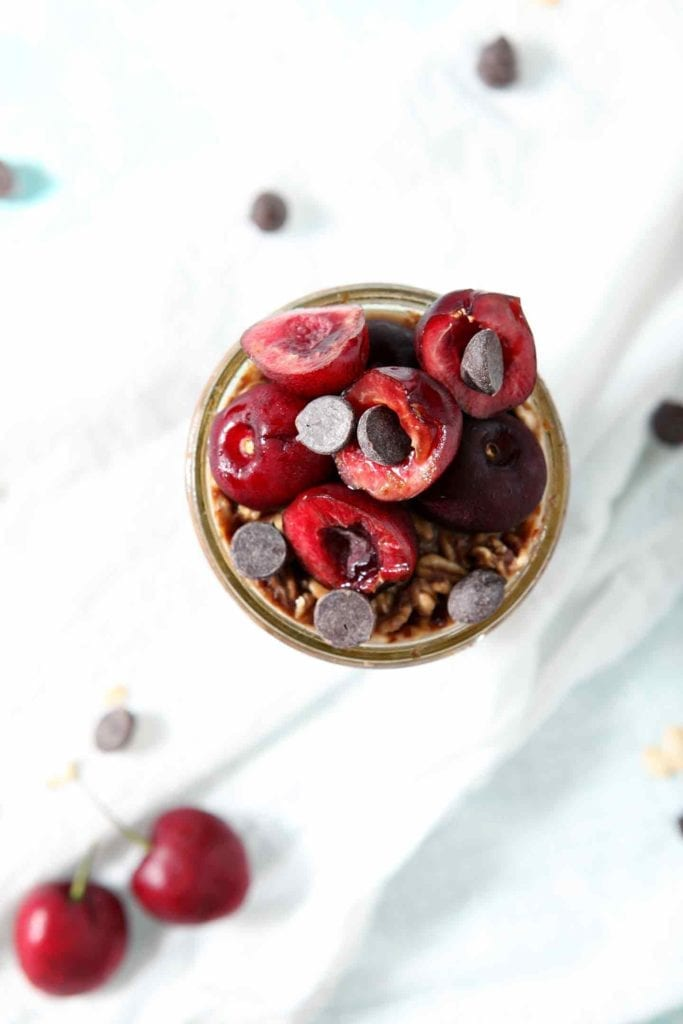 Close up of Cherry Overnight Oats from above, highlighting the fresh cherries and chocolate chips used as toppings