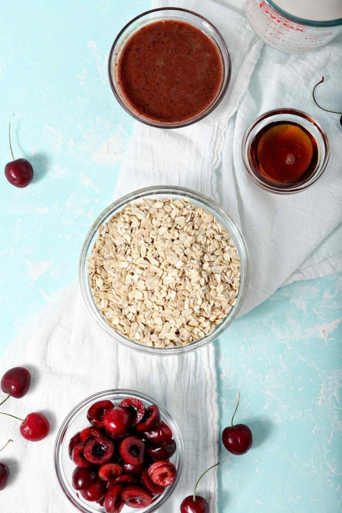 The six ingredients for Cherry Overnight Oats, shown on a turquoise background