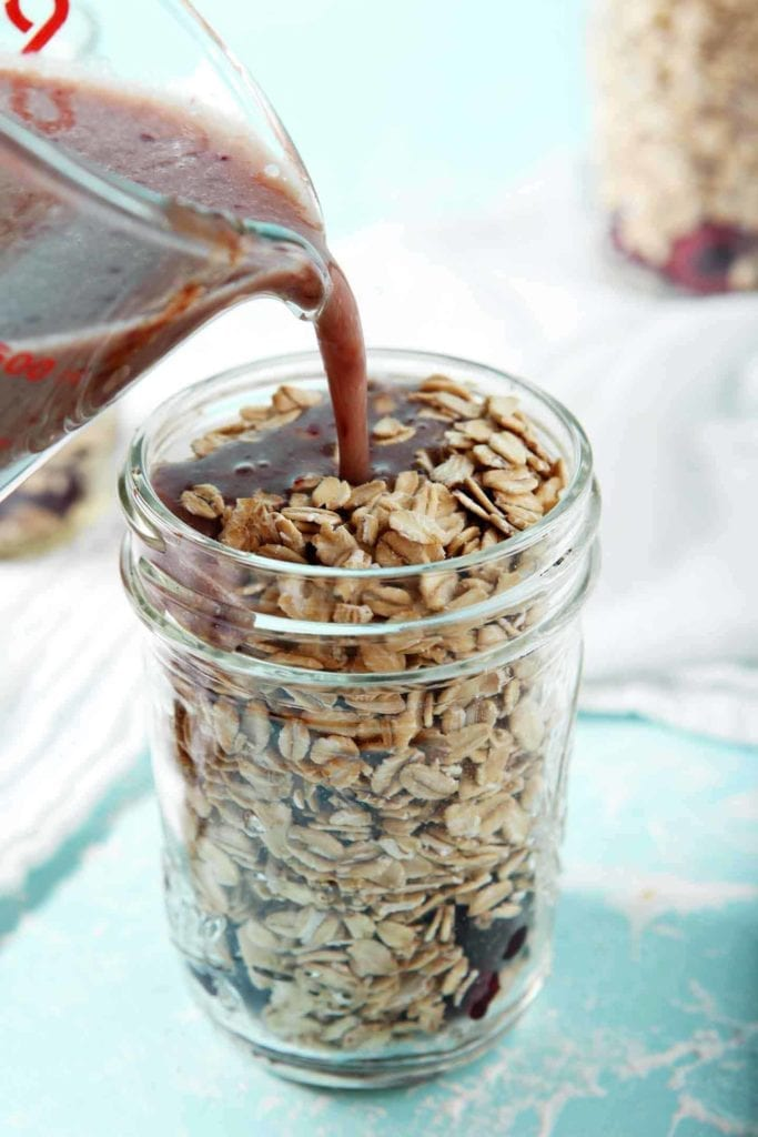 A mixture of cashew milk, maple syrup and cherry puree are poured in top of rolled oats to make overnight oats