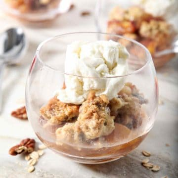 Several servings of Dairy Free Peach Cobbler, topped with dairy free ice cream, sit on a marble background before serving