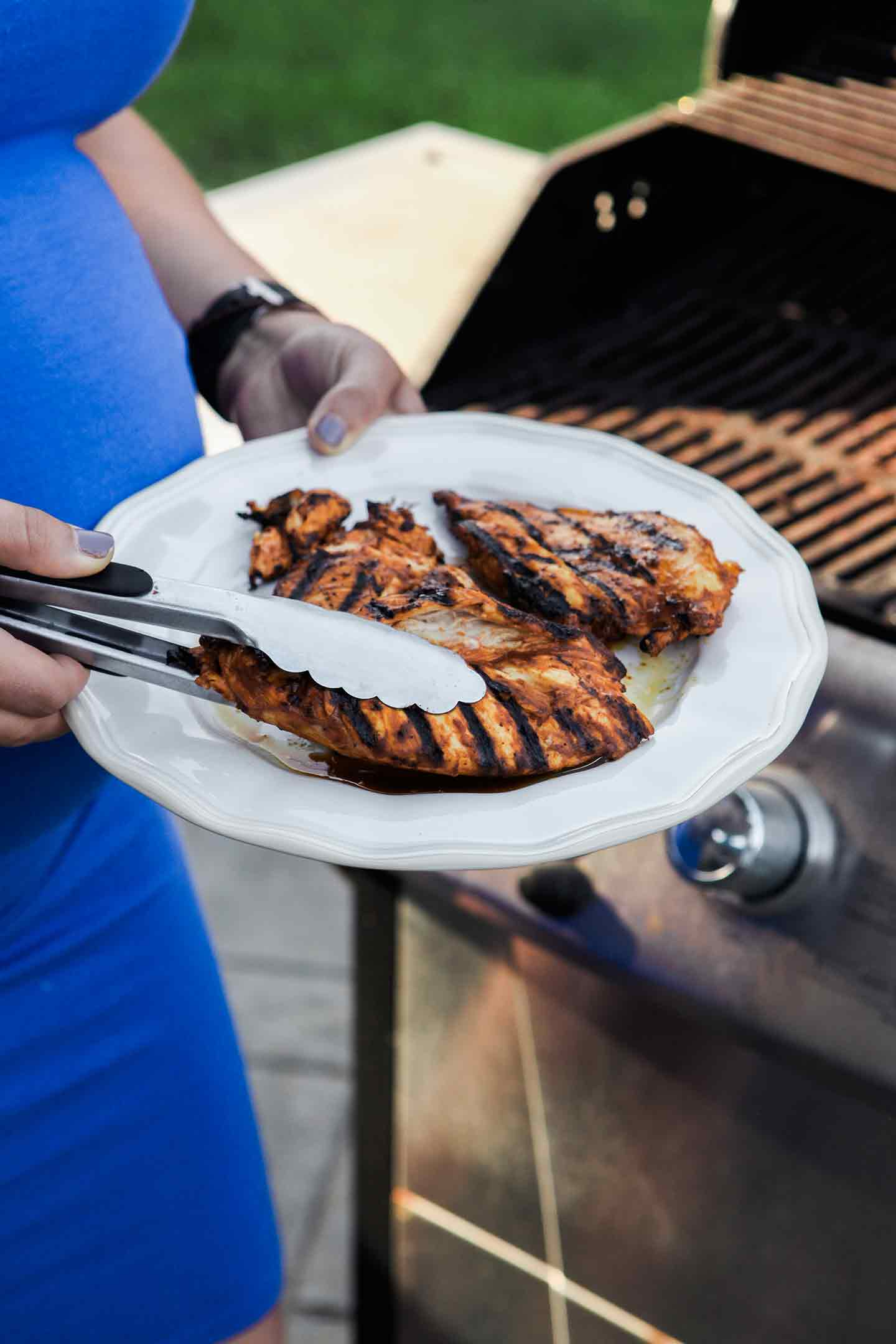 A woman holds barbecue chicken next to the grill