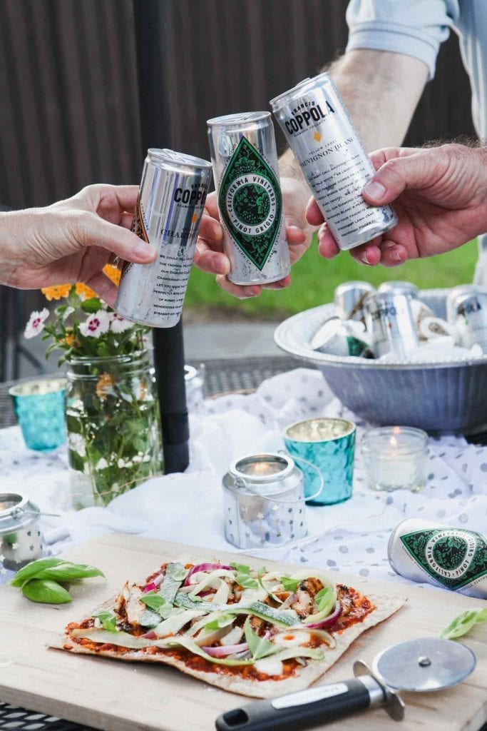Three people clink Coppola Diamond Collection cans together at an outdoor gathering.