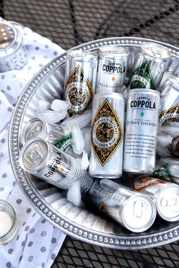 Coppola Diamond Collection cans sit in a silver ice bucket at an outdoor gathering