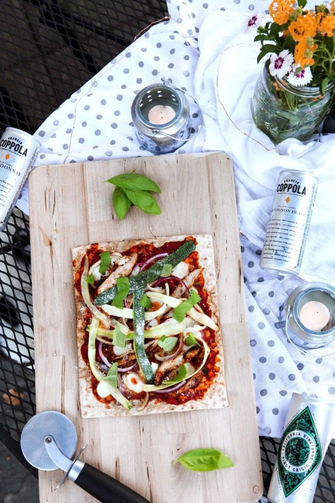 A Grilled BBQ Chicken Flatbread, straight off the grill, sits on an outdoor table, ready for serving.