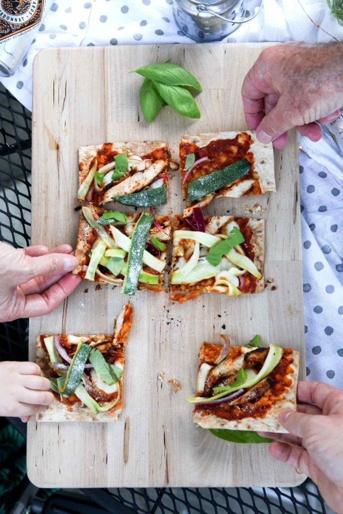 Four people grab for slices of Grilled BBQ Chicken Flatbread, straight off the grill