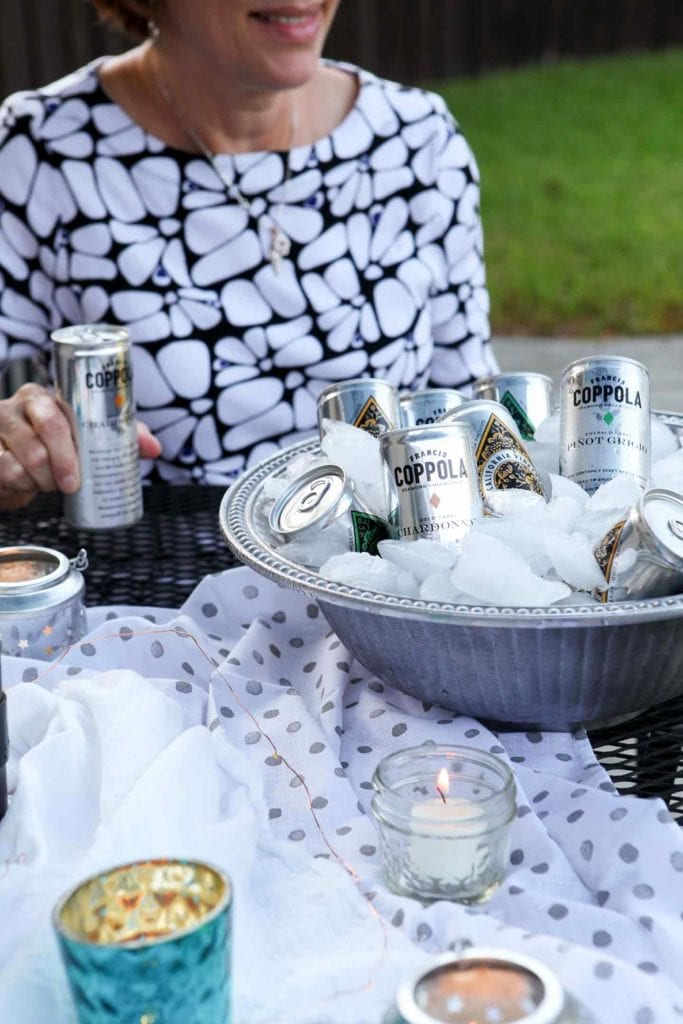 A woman holds a Coppola Diamond Collection can and sits next to the silver ice bucket holding more at an outdoor gathering