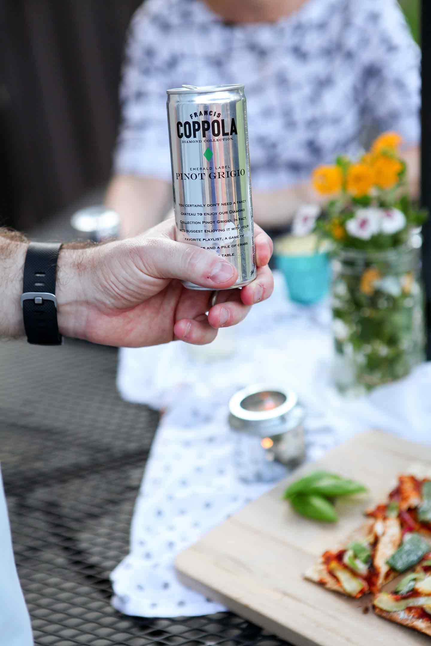 A man holds a Coppola Diamond Collection can at an outdoor gathering