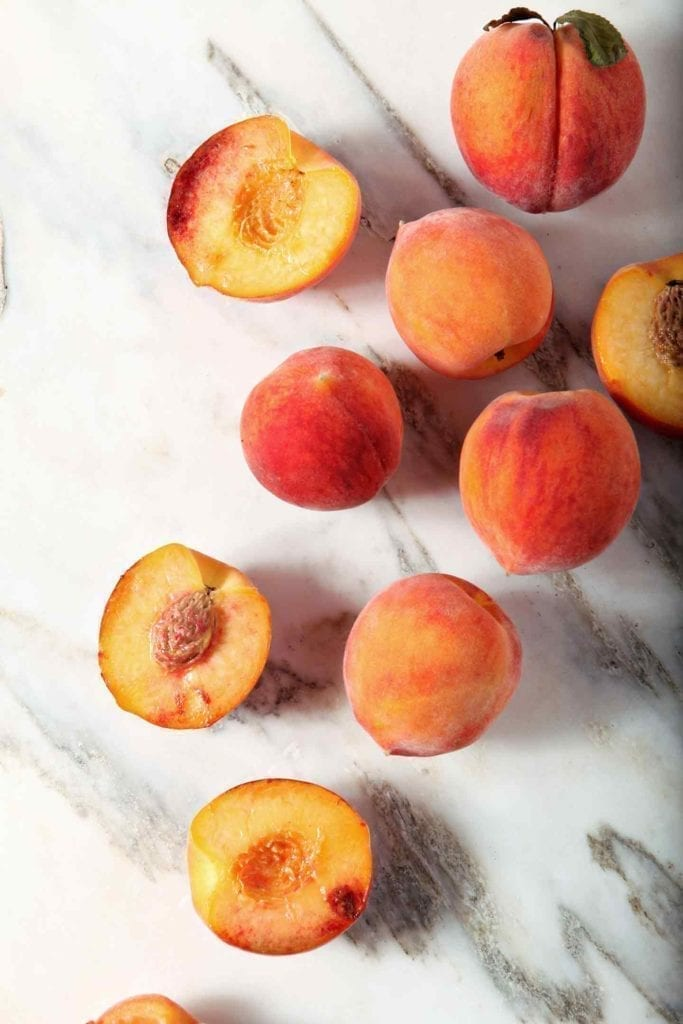 Some whole and some halved peaches on marble